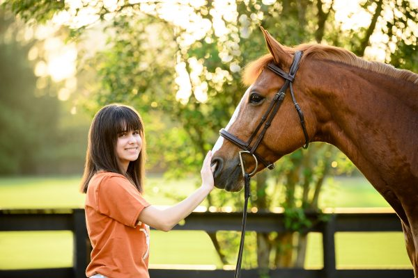 teenager in orange shirt with chestnut horse