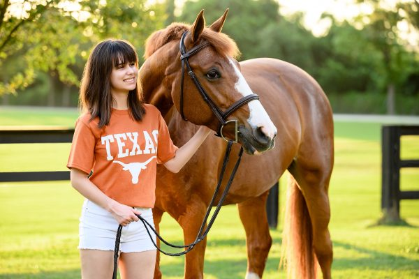 teenager in University of Texas shirt with chestnut horse