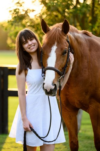 teenager in white dress with chestnut horse
