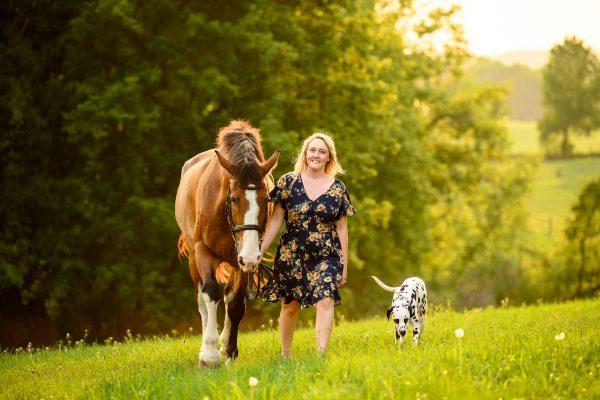 woman walking with bay horse and Dalmatian