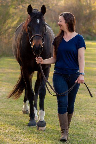woman walking with dark bay horse